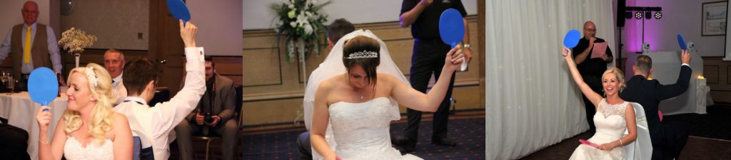 3 brides playing Mr and Mrs game, holding blue paddles