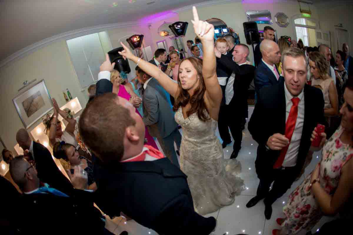 Bride with hands in the air in the centre of the dancefloor, surrounded by family members and friends