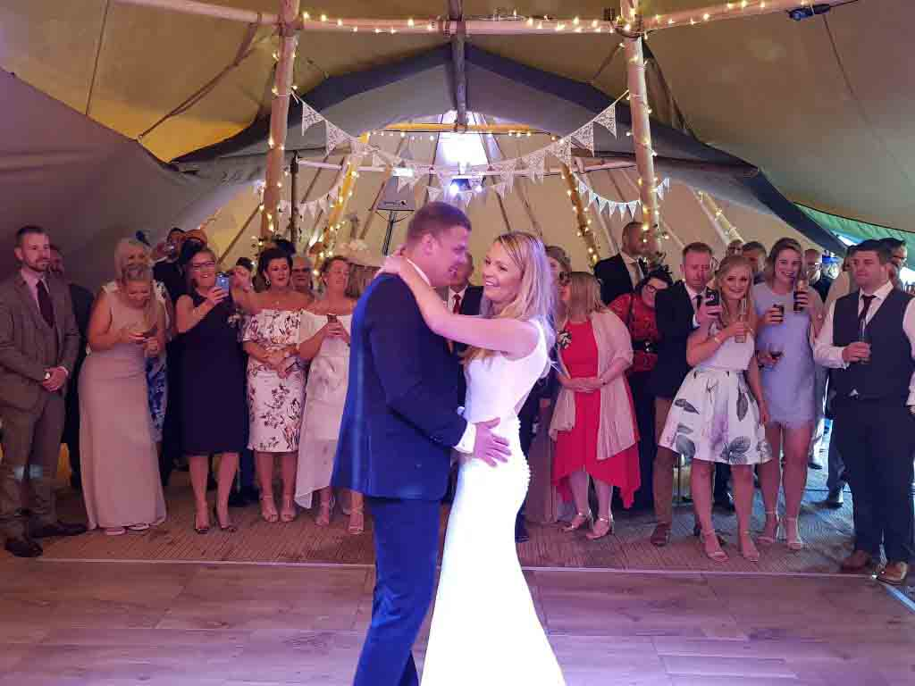 Happy couple taking their first dance in front of their families and friends.